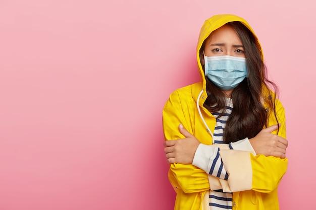 Mulher asiática chateada treme de frio, tem vírus transmitido por gotículas no osso do ar, usa máscara médica protetora, capa de chuva amarela com capuz