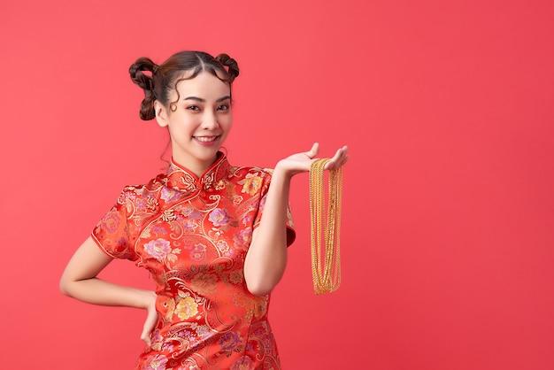 Mulher asiática chinesa atraente no vestido tradicional está segurando o colar de ouro com alegria e alegre. feliz ano novo chinês. conceito de desejo.