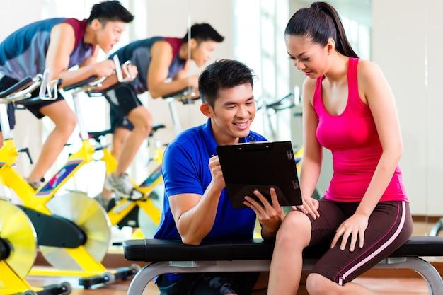 Mulher asiática chinesa e personal trainer na academia discutindo cronograma de treinamento e metas para o treino
