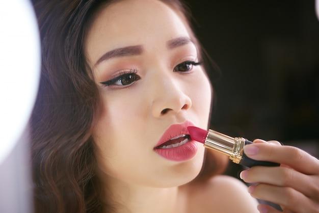 Mulher asiática chique se preparando para terminar a maquiagem dos lábios com batom vermelho