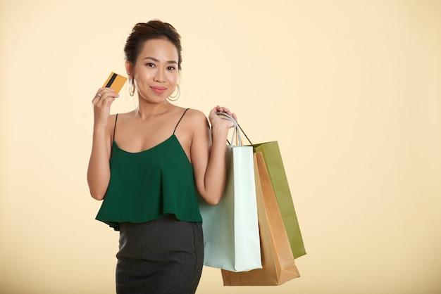 Mulher asiática chique sorridente posando com sacolas de compras e cartão de crédito