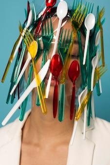 Mulher asiática coberta de talheres de plástico coloridos
