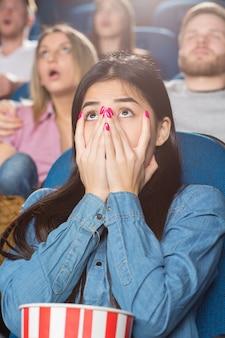 Mulher asiática, cobrindo a boca com as mãos apavorada assistindo a um filme no cinema