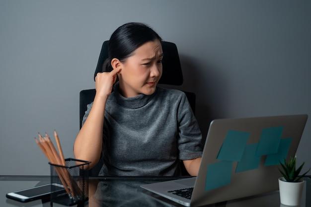 Mulher asiática coçando e colocando um dedo na orelha, trabalhando em um laptop no escritório