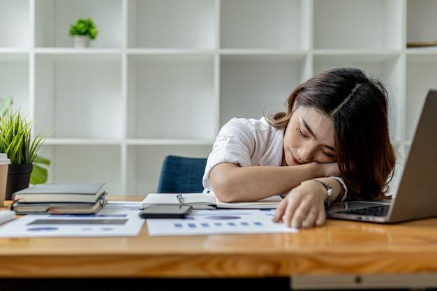 Mulher asiática cochilando em sua mesa, empresária cochilando em sua mesa depois de trabalhar por um longo tempo, causando fadiga e sonolência, ela está descansando. conceito de trabalho duro.