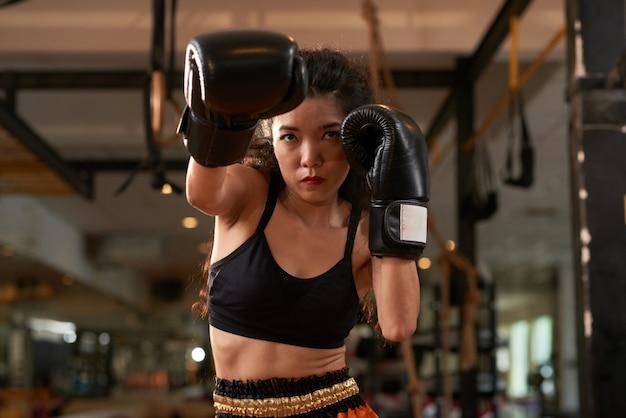 Mulher asiática colhida treinando em luvas de boxe na prática de muay thai