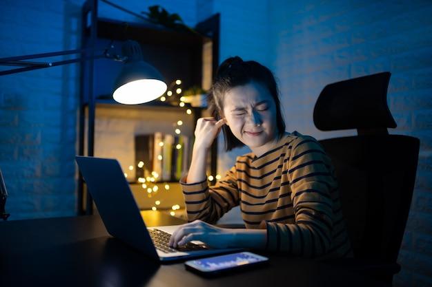 Mulher asiática colocando um dedo em seu ouvido e trabalhando em um laptop horas extras em casa. . trabalhe em casa para evitar o conceito covid 19 do coronavírus.