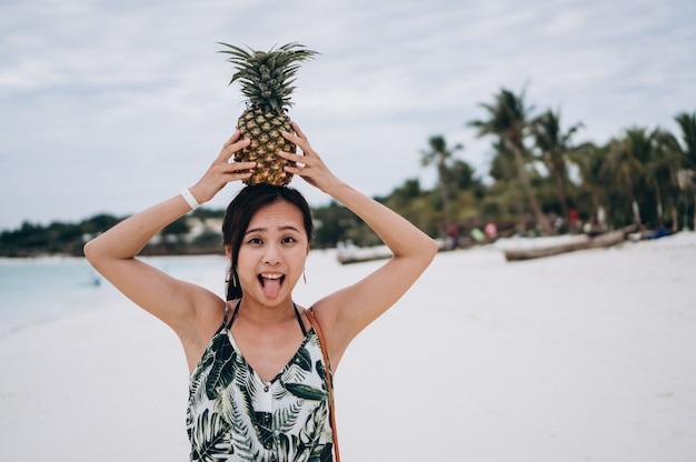 Mulher asiática com abacaxi na praia