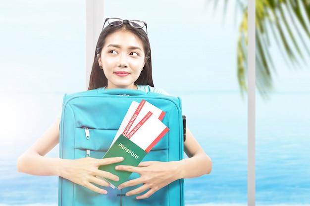 Mulher asiática com bilhete e passaporte, apoiando-se na mala no resort