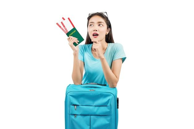 Mulher asiática com bilhete e passaporte, apoiando-se na mala