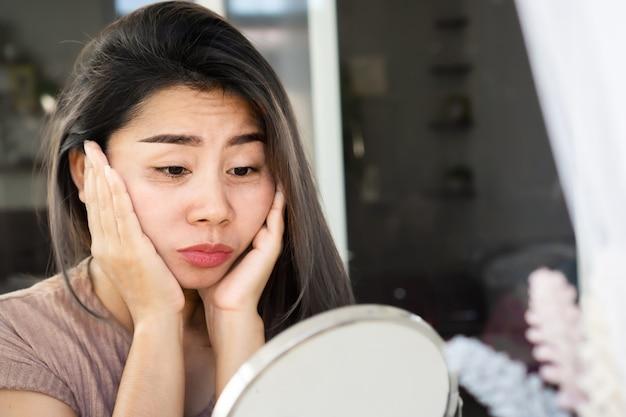 Mulher asiática com bolsas nos olhos, olheiras, rugas e pés de galinha no rosto
