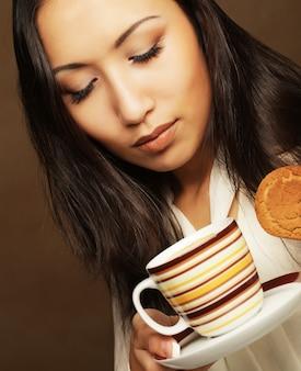Mulher asiática com café e biscoitos.