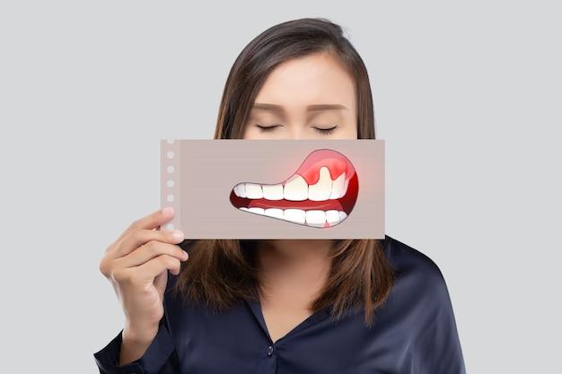 Mulher asiática com camisa azul escura segurando um papel com a imagem de periodontal e gengivite de sua boca contra o fundo cinza