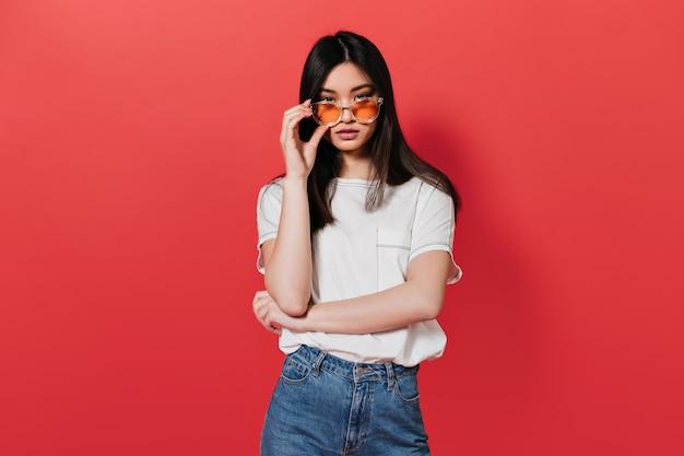 Mulher asiática com camiseta branca tirando os óculos de sol