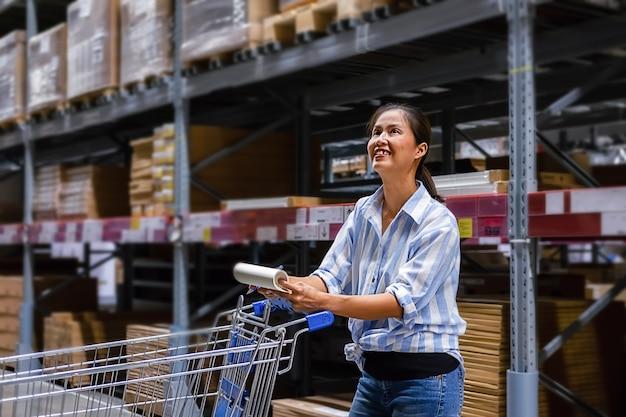 Mulher asiática com carrinho de mercado na loja de móveis
