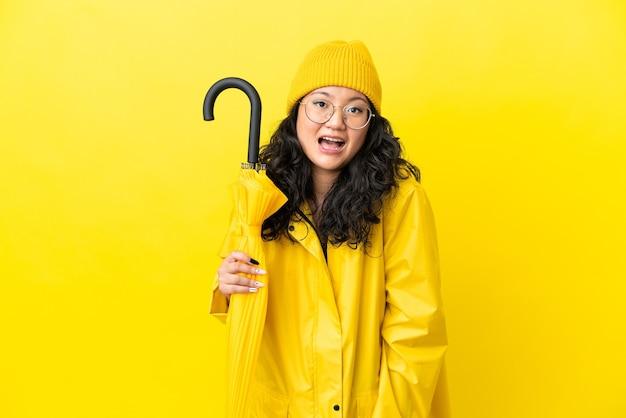 Mulher asiática com casaco à prova de chuva e guarda-chuva isolado em um fundo amarelo com expressão facial surpresa