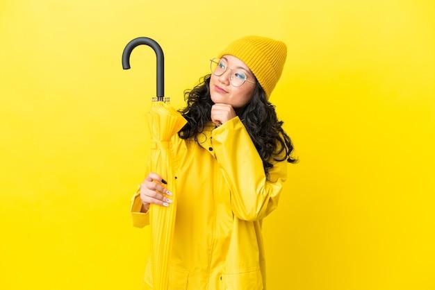 Mulher asiática com casaco à prova de chuva e guarda-chuva isolado em um fundo amarelo e olhando para cima