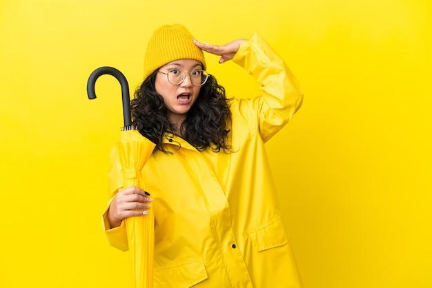 Mulher asiática com casaco à prova de chuva e guarda-chuva isolado em um fundo amarelo fazendo gesto surpresa enquanto olha para o lado