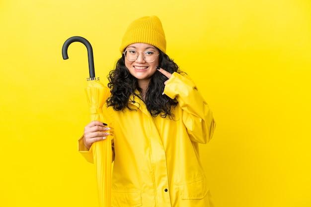 Mulher asiática com casaco à prova de chuva e guarda-chuva isolado em um fundo amarelo fazendo um gesto de polegar para cima