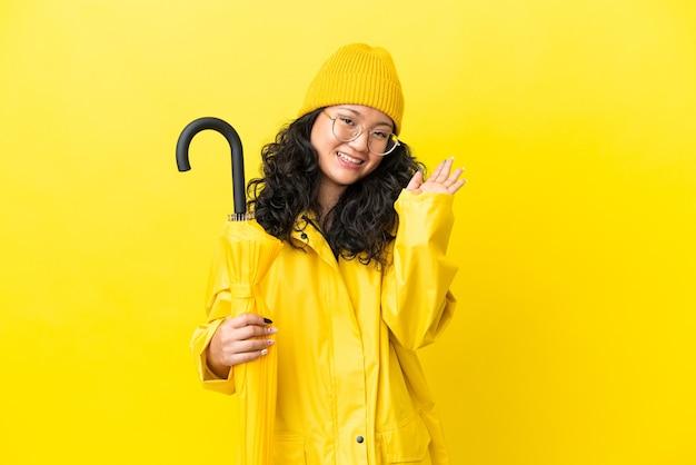 Mulher asiática com casaco à prova de chuva e guarda-chuva isolado em um fundo amarelo saudando com a mão com expressão feliz