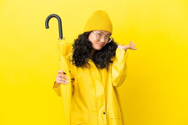Mulher asiática com casaco à prova de chuva e guarda-chuva isolado em um fundo amarelo, tendo dúvidas ao levantar as mãos