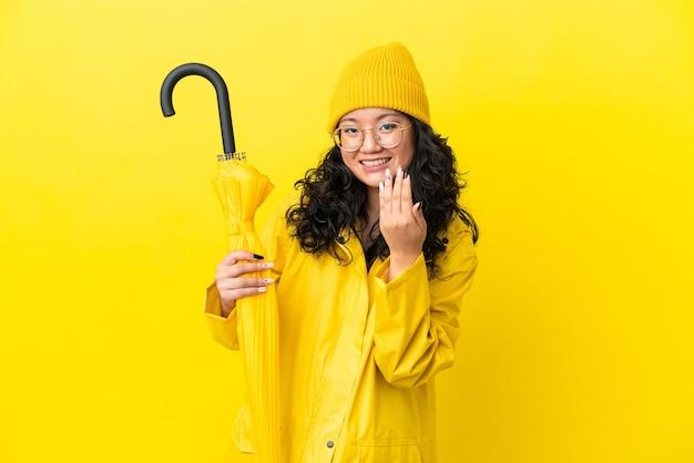Mulher asiática com casaco à prova de chuva e guarda-chuva isolado no fundo amarelo, convidando para vir com a mão. feliz que você veio