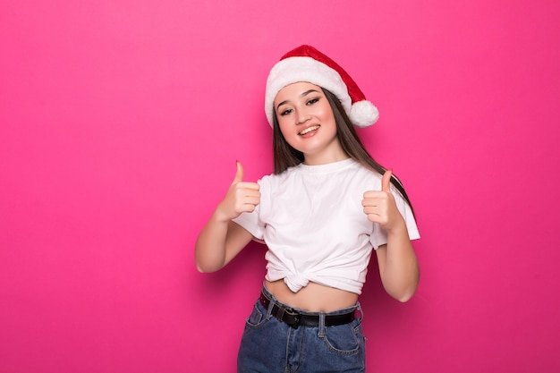 Mulher asiática com chapéu de papai noel com polegar para cima isolado na parede rosa