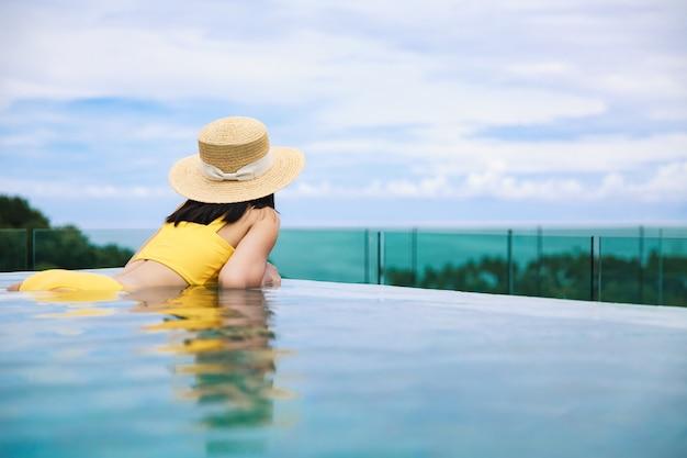 Mulher asiática com chapéu e biquíni relaxa em resort com piscina infinita em phuket, tailândia