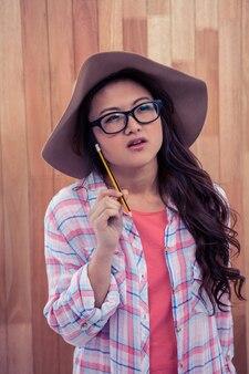 Mulher asiática com chapéu segurando o lápis contra a parede de madeira