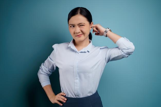 Mulher asiática com coceira e colocando um dedo nas orelhas em pé isolado em azul.