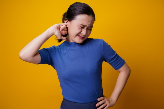 Mulher asiática com coceira e colocando um dedo nas orelhas em pé sobre amarelo.