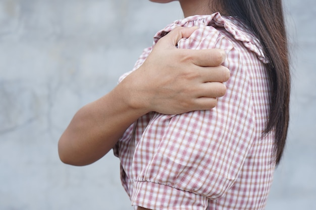 Mulher asiática com coceira no ombro