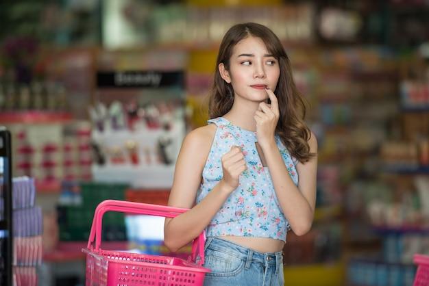 Mulher asiática com coisa de compra da cesta na loja da beleza.