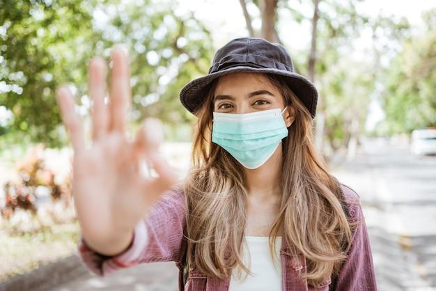 Mulher asiática com coronavírus colocando uma máscara médica descartável para evitar vírus
