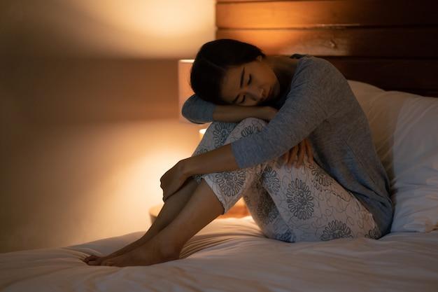 Mulher asiática com distúrbio do sono na cama