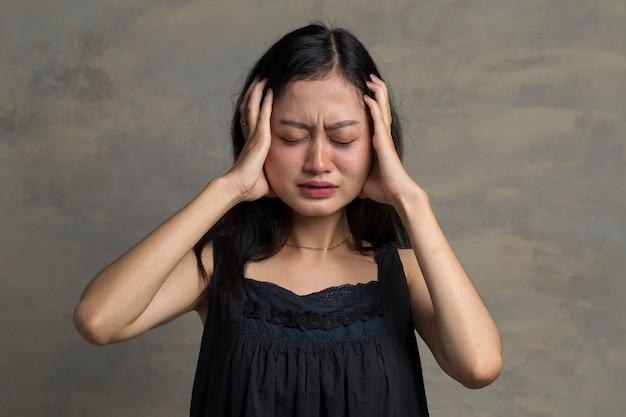 Mulher asiática com dor de cabeça