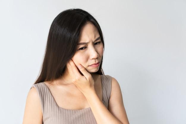 Mulher asiática com dor de dente. close da menina triste, sofrendo de dor de dente. linda mulher sentindo dor de dente dolorida em fundo branco. saúde e cuidados dentários, problema de dentes. copie o espaço