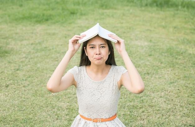Mulher asiática com emoção entediada com um livro em cima da cabeça no fundo do chão de grama turva