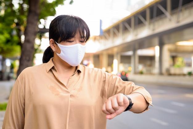Mulher asiática com excesso de peso com máscara para proteção contra surto de vírus corona, verificando o tempo nas ruas da cidade