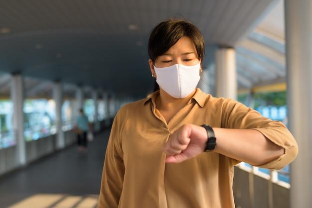 Mulher asiática com excesso de peso com máscara, verificando o tempo na cidade