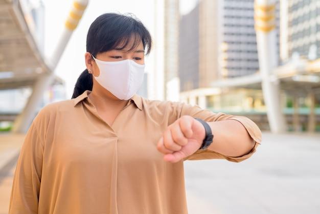 Mulher asiática com excesso de peso com máscara, verificando o tempo na ponte da passarela