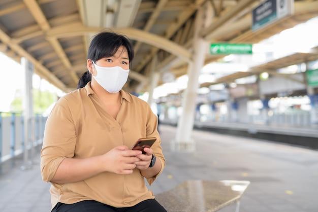 Mulher asiática com excesso de peso com pensamento de máscara enquanto estiver usando o telefone na estação de trem do céu