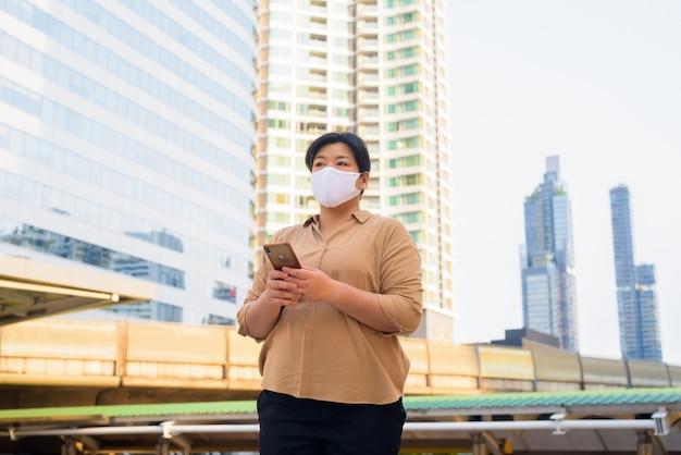 Mulher asiática com excesso de peso com pensamento de máscara enquanto estiver usando o telefone na ponte skywalk