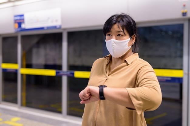 Mulher asiática com excesso de peso, verificando o tempo com máscara para proteção contra surto de vírus corona na estação de trem do metrô