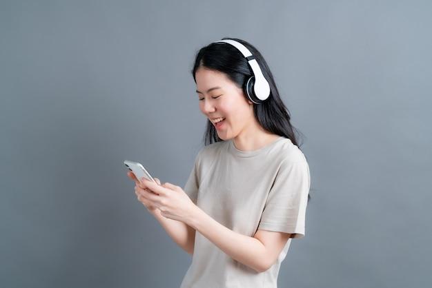 Mulher asiática com fone de ouvido sem fio segura smartphone olhando para a tela do telefone usando o aplicativo do player móvel, ouvindo música online, aprendendo um idioma estrangeiro, assistindo a um vídeo relaxante na parede cinza