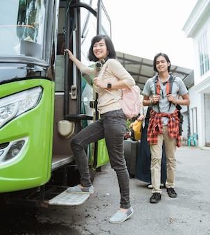 Mulher asiática com fones de ouvido e bolsa sorrindo ao entrar no ônibus para ir de férias
