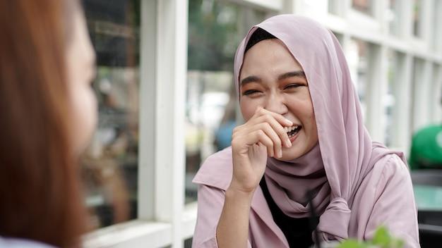 Mulher asiática com hijab sorrindo em um café com uma amiga