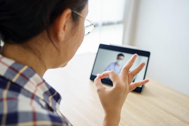 Mulher asiática com idade entre 30-35 anos usando um tablet. ver os resultados dos exames dos médicos