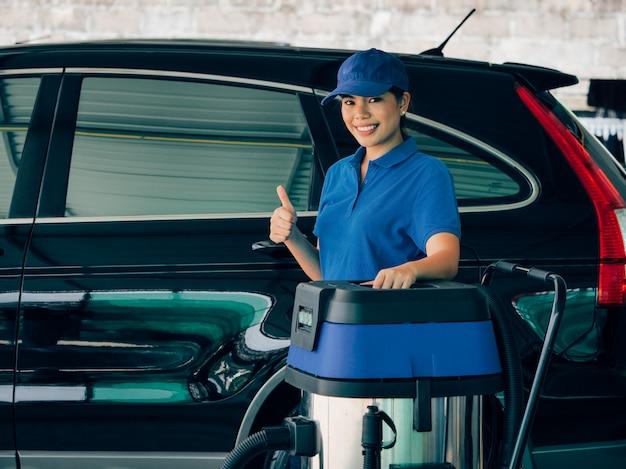 Mulher asiática com lavar a máquina do carro.