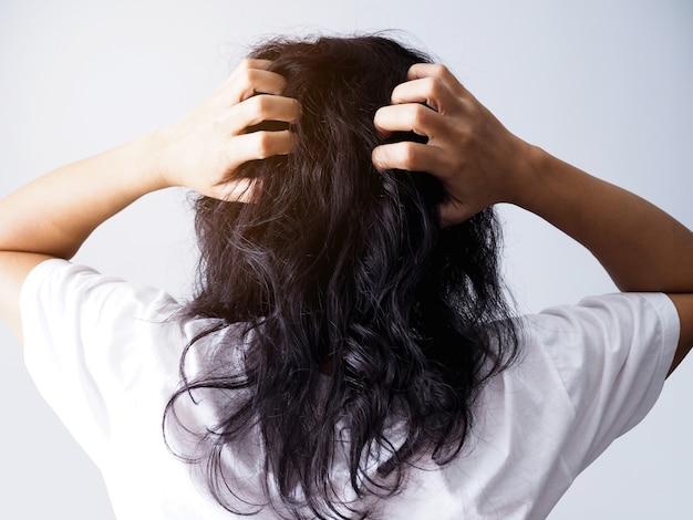 Mulher asiática com longos cabelos negros coçando a cabeça de coceira e ter cabelos desarrumados.